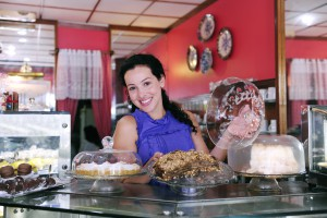 owner of a small business/ delicatessen store/ cafe showing her tasty cakes